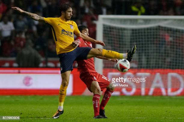 Sime Vrsaljko of Atletico de Madrid fights for the ball with Rubens Sambueza during a friendly match between Toluca and Atletico de Madrid as part of...
