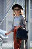 Simge Ozgoren poses wearing cardigan by BSL tshirt by HM Studiopants and hat by HM hand bag by Balenciaga sunglasses by Komono watch by Daniel...