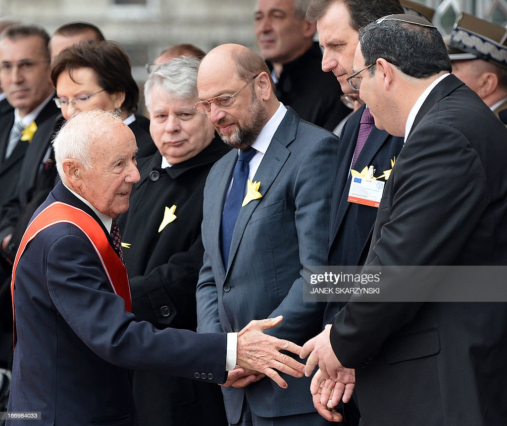 Simha 'Kazik' Rotem (L), one of the last living Warsaw Ghetto insurgents shakes hands with Israeli Education Minister Shai Piron (R) next to Chairman of Parliament Bogdan Borusewicz (2ndL) and President of European Parliament Martin Schulz in front of the Warsaw Ghetto Uprising monument, during the ceremonies held 70 years to the day of the ghetto uprising against the Nazi Germany in Warsaw on April 19, 2013. SKARZYNSKI
