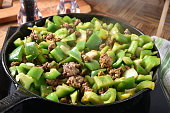 Seasoned ground beef and diced green peppers simmering in a cast iron skillet