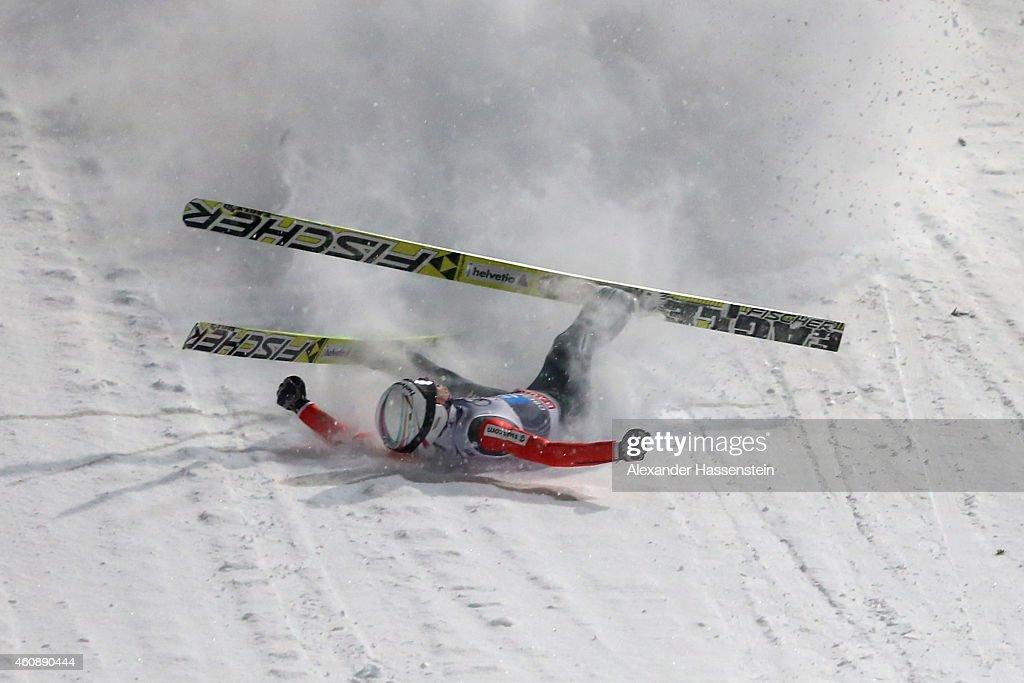 Simon Ammann of Switzerland falls on his first round jump on day 2 of the Four Hills Tournament Ski Jumping event at SchattenbergSchanze Erdinger...