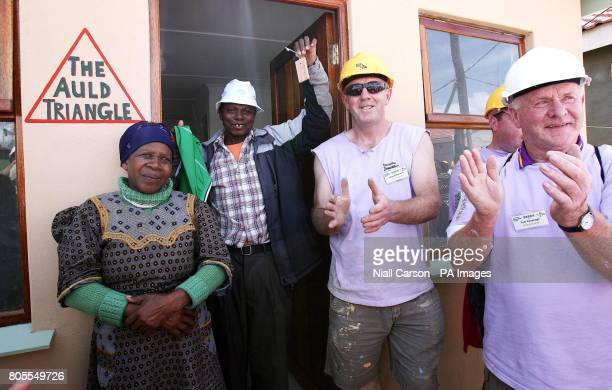 Simon and Emeli Ntsitshe celebrate after receiving the keys to their first home in Wallacdene Township in Capetown after living in a shack for 13...