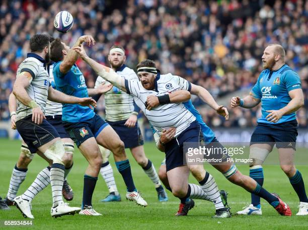 Simon Berghan of Scotland is tackled by Dries van Schalkwyk of Italy and Tommaso Benvenuti of italy trying to intercept the ball as Alex Dunbar and...