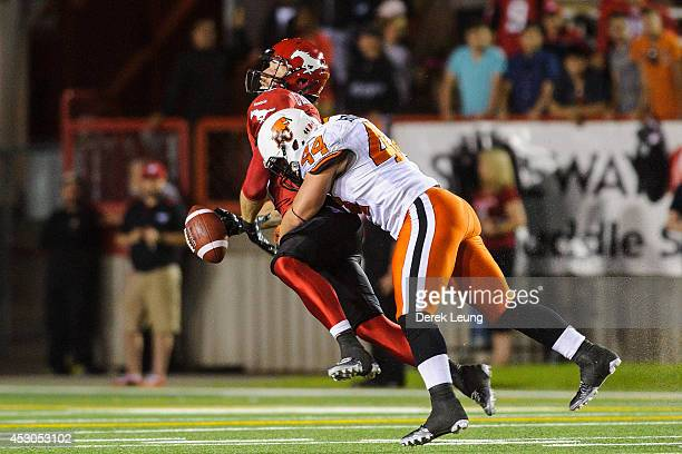 Simon CharbonneauCampeau of the Calgary Stampeders gets tackled by Adam Bighill of the BC Lions during a CFL game at McMahon Stadium on August 1 2014...