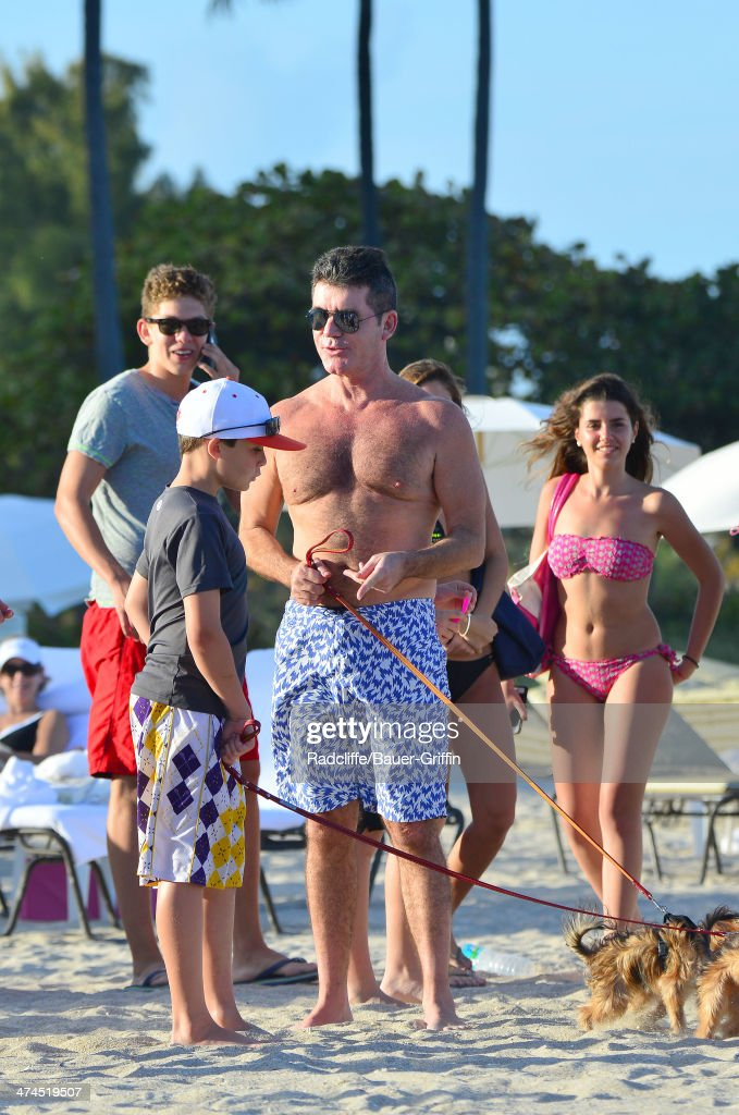 Simon Cowell is seen talking with fans while walking his dogs at the beach on February 23, 2014 in Miami, Florida.