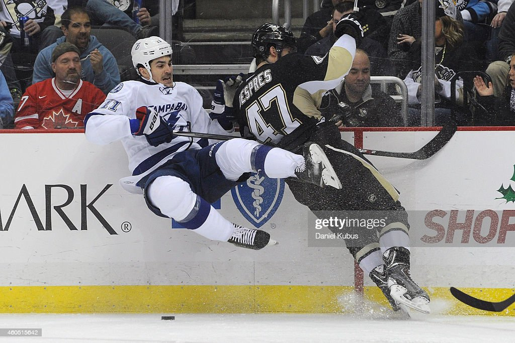 Simon Despres #47 of the Pittsburgh Penguins hits <a gi-track='captionPersonalityLinkClicked' href=/galleries/search?phrase=Brian+Boyle+-+Ishockeyspelare&family=editorial&specificpeople=8986264 ng-click='$event.stopPropagation()'>Brian Boyle</a> #11 of the Tampa Bay Lightning in the second period at Consol Energy Center on December 15, 2014 in Pittsburgh, Pennsylvania.