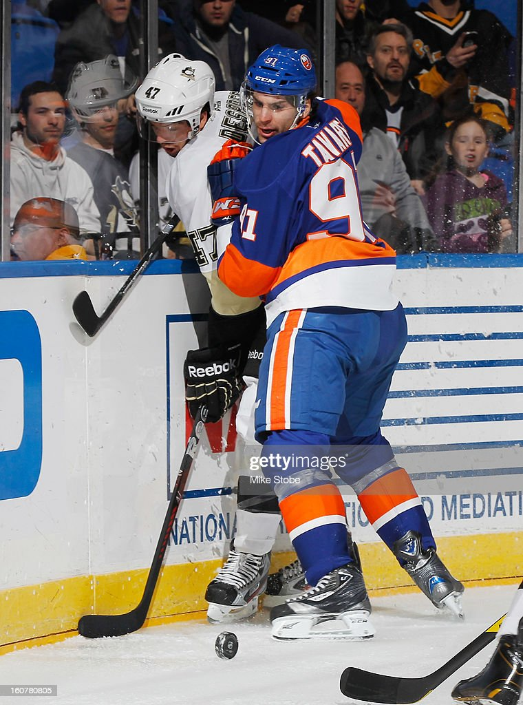 Simon Despres #47 of the Pittsburgh Penguins is checked into the boards by John Tavares #91 of the New York Islanders at Nassau Veterans Memorial Coliseum on Febuary 5, 2013 in Uniondale, New York.