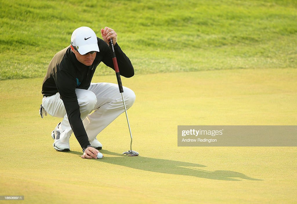 Simon Dyson of England marks his ball on the 15th hole during the second round of the BMW Masters at Lake Malaren Golf Club on October 25, 2013 in Shanghai, China.