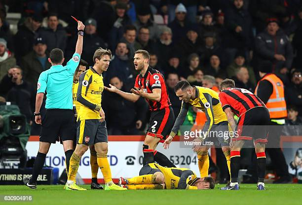Simon Francis of AFC Bournemouth reacts after receiving a red card by referee Michael Oliver after tackling on Aaron Ramsey of Arsenal during the...