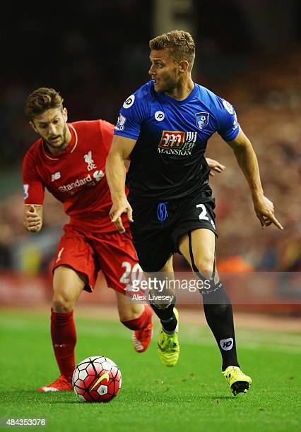 Simon Francis of Bournemouth is chased by Adam Lallana of Liverpool during the Barclays Premier League match between Liverpool and AFC Bournemouth at...