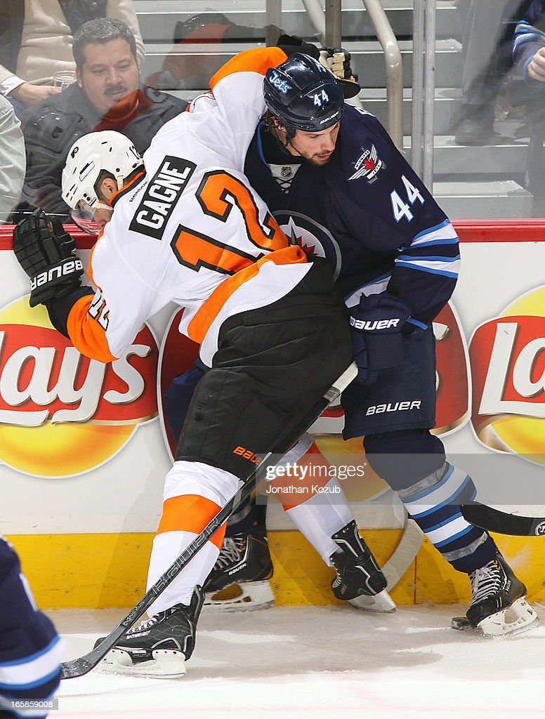 Simon Gagne #12 of the Philadelphia Flyers pins Zach Bogosian #44 of the Winnipeg Jets to the boards as they battle for the puck during second period action at the MTS Centre on April 6, 2013 in Winnipeg, Manitoba, Canada.