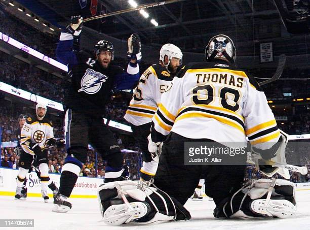 Simon Gagne of the Tampa Bay Lightning celebrates a goal by Teddy Purcell as Tim Thomas of the Boston Bruins defends in Game Six of the Eastern...