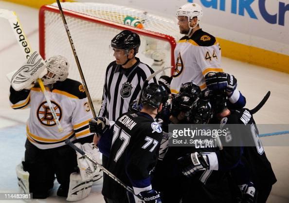 Simon Gagne of the Tampa Bay Lightning celebrates scoring a third period goal with teammates as Tim Thomas and Dennis Seidenberg of the Boston Bruins...