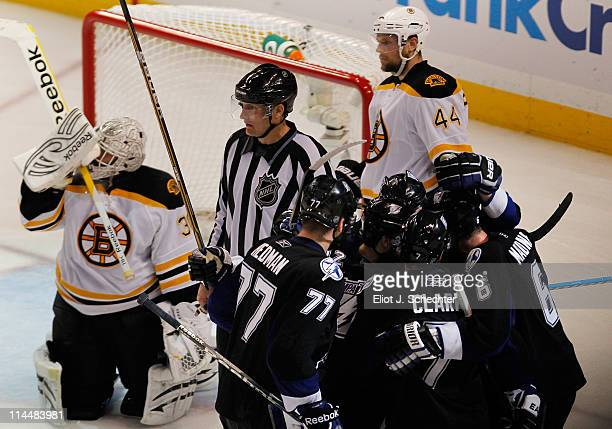 Simon Gagne of the Tampa Bay Lightning celebrates scoring a third period goal with teammates as Tim Thomas and Dennis Seidenberg of the Boston Bruins...