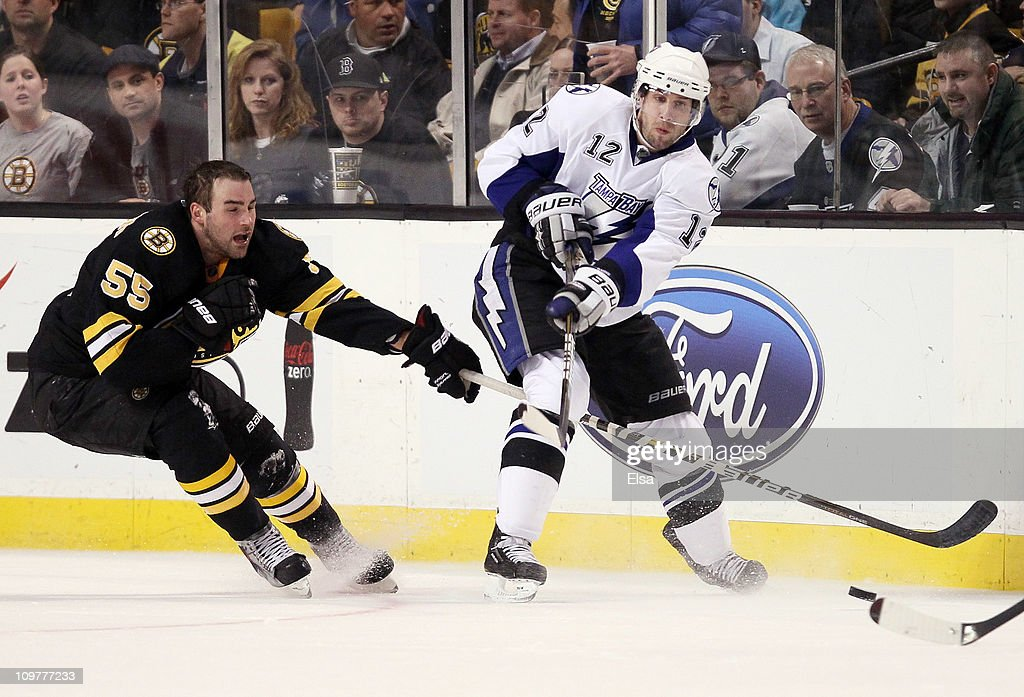 Simon Gagne #12 of the Tampa Bay Lightning passes the puck as Johnny Boychuk #55 of the Boston Bruins defends on March 3, 2011 at the TD Garden in Boston, Massachusetts. The Boston Bruins defeated the Tampa Bay Lightning 2-1.