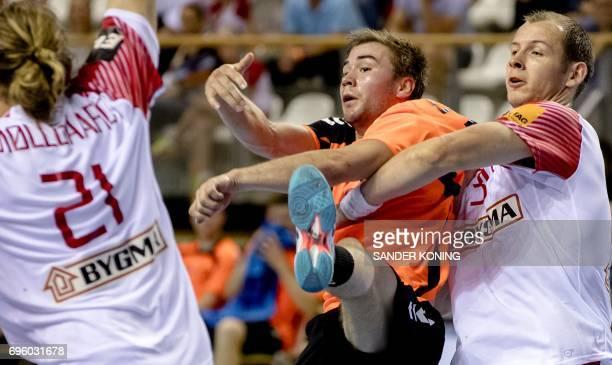 Simon Hald Jensen of Denmark holds Luc Steins of The Netherlands during the EC qualification handball match Denmark vs Netherlands in Almere on June...