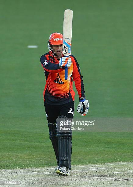 Simon Katich of the Scorchers raises his bat after he scored his half century during the Big Bash League match between the Hobart Hurricanes and the...