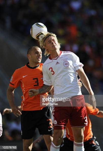 Simon Kjaer of Denmark heads the ball with John Heitinga of the Netherlands during the 2010 FIFA World Cup Group E match between Netherlands and...