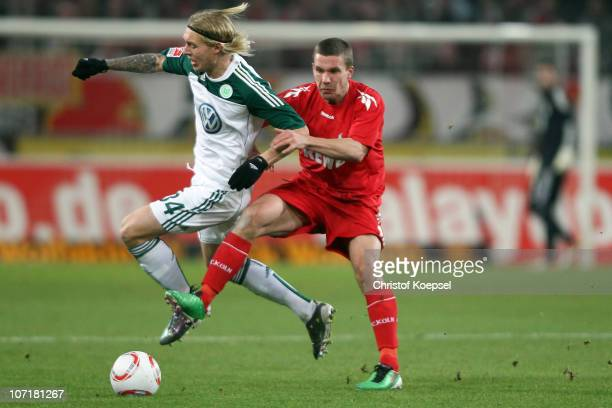 Simon Kjaer of Wolfsburg challenges Lukas Podolski of Koeln during the Bundesliga match between 1 FC Koeln and VfL Wolfsburg at RheinEnergieStadion...