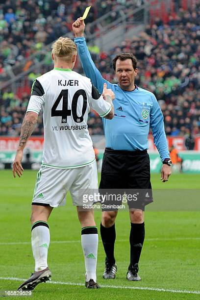 Simon Kjaer of Wolfsburg is booked yellow card by referee Peter Sippel during the Bundesliga match between Bayer 04 Leverkusen and VfL Wolfsburg at...