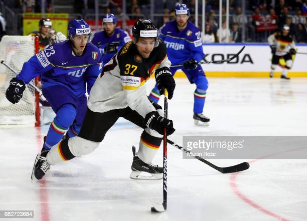 Simon Kostner of Italy challenges Patrick Reimer of Germany for the puck during the 2017 IIHF Ice Hockey World Championship game between Italy and...