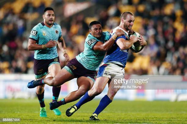 Simon Mannering of the Warriors is tackled by George Fai of the Broncos during the round 12 NRL match between the New Zealand Warriors and the...