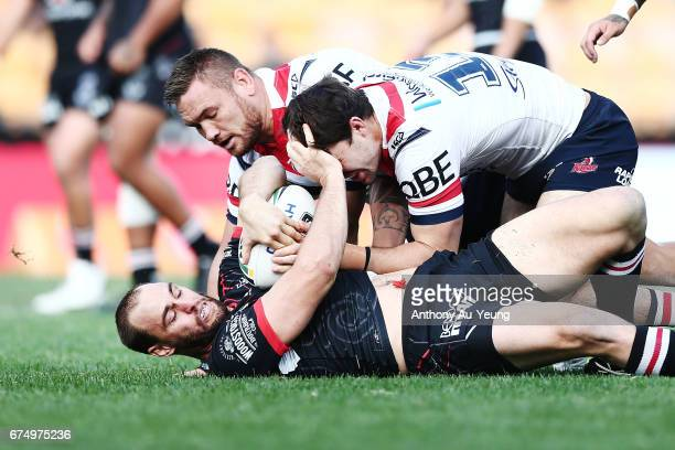 Simon Mannering of the Warriors is tackled by Jared WaereaHargreaves and Aidan Guerra of the Roosters during the round nine NRL match between the New...