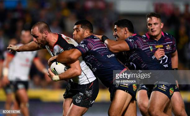 Simon Mannering of the Warriors is tackled by John Asiata and Jason Taumalolo of the Cowboys during the round 20 NRL match between the North...