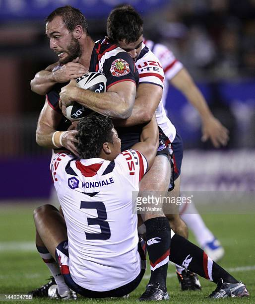Simon Mannering of the Warriors is tackled by Joseph Leilua of the Roosters during the round 10 NRL match between the New Zealand Warriors and the...