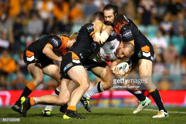 Simon Mannering of the Warriors is tackled during the round 26 NRL match between the Wests Tigers and the New Zealand Warriors at Leichhardt Oval on...