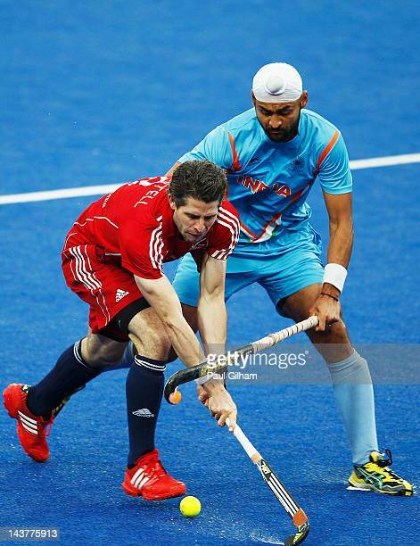 Simon Mantell of Great Britain battles for the ball with Sandeep Singh of India during the Men's preliminary match between Great Britain and India...