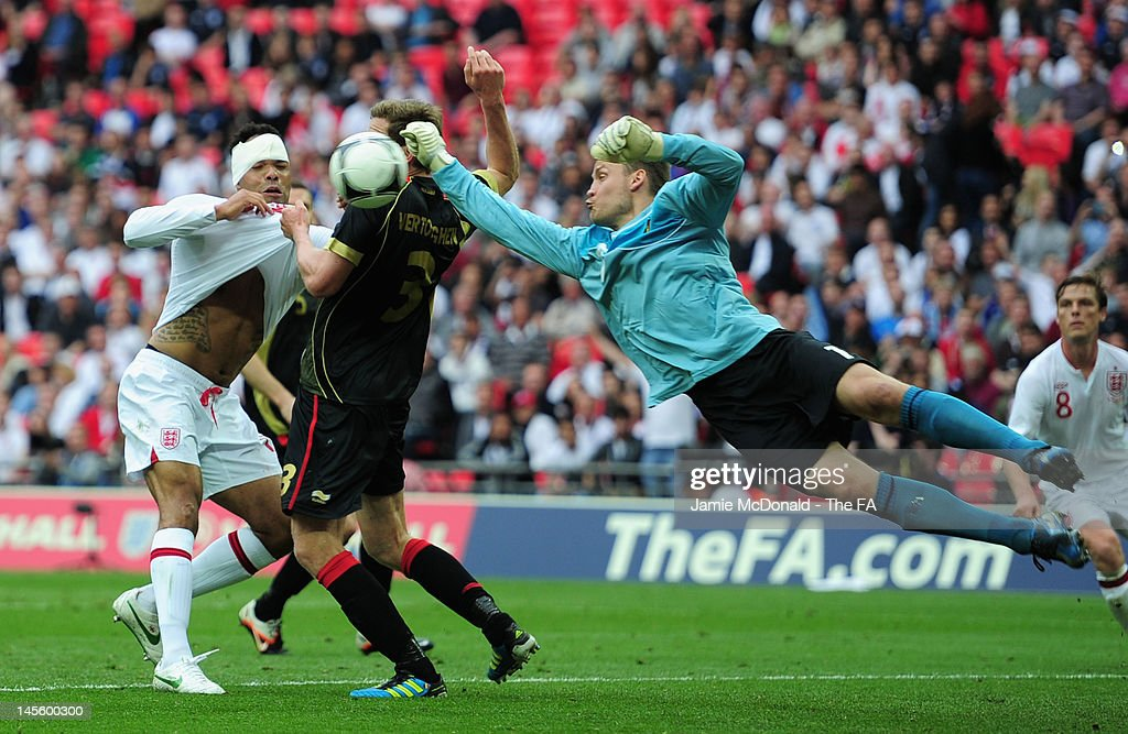 Simon Mignolet of Belgium punches clear under pressure from <a gi-track='captionPersonalityLinkClicked' href=/galleries/search?phrase=Joleon+Lescott&family=editorial&specificpeople=687246 ng-click='$event.stopPropagation()'>Joleon Lescott</a> of England during the International Friendly match between England and Belgium at Wembley Stadium on June 2, 2012 in London, England.