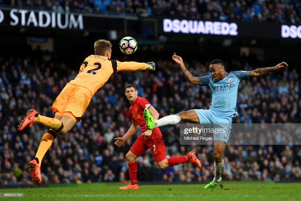 Simon Mignolet of Liverpool (L) attempts to punch the ball as Raheem Sterling of Manchester City (R) attempts to score during the Premier League match between Manchester City and Liverpool at Etihad Stadium on March 19, 2017 in Manchester, England.
