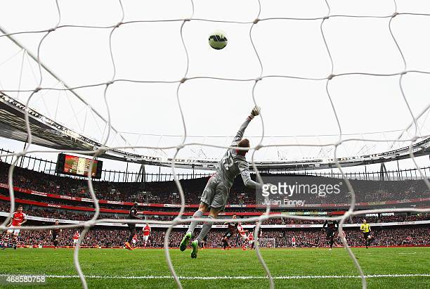 Simon Mignolet of Liverpool jumps in vain as Alexis Sanchez of Arsenal scores his team's third goal during the Barclays Premier League match between...