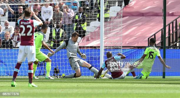 Simon Mignolet of Liverpool makes a save from Andre Ayew of West Ham United during the Premier League match between West Ham United and Liverpool at...