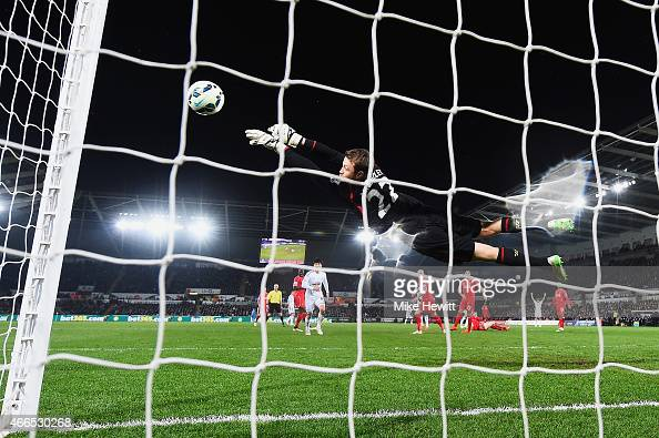 Simon Mignolet of Liverpool makes a save from Gylfi Sigurdsson of Swansea City during the Barclays Premier League match between Swansea City and...