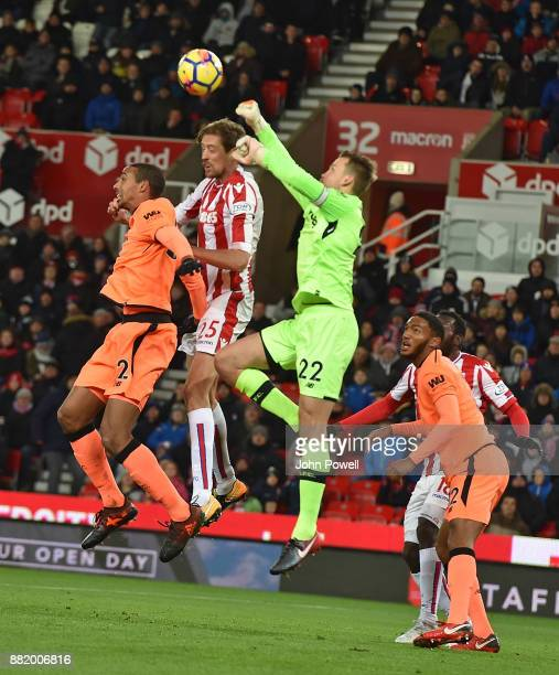 Simon Mignolet of Liverpool punches the ball away from Peter Crouch of Stoke City during the Premier League match between Stoke City and Liverpool at...