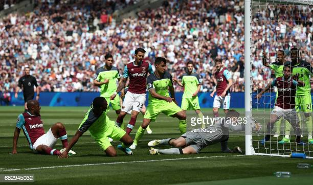 Simon Mignolet of Liverpool saves a shot from Andre Ayew of West Ham United during the Premier League match between West Ham United and Liverpool at...