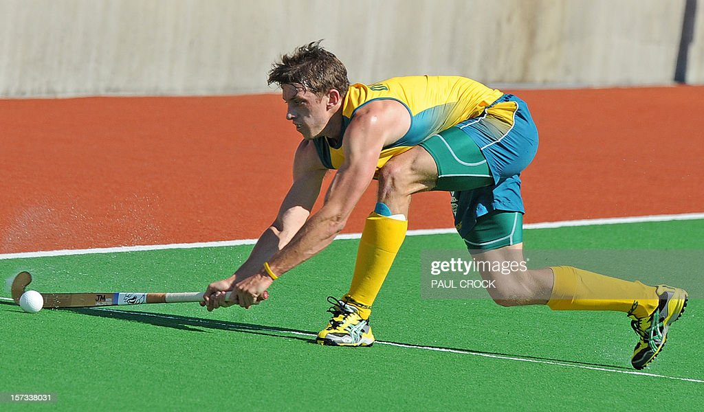 Simon Orchard of Australia (C) cracks the ball down the pitch during their Pool B match against the Netherlands at the Men's Hockey Champioships Trophy in Melbourne on December 2, 2012. IMAGE STRICTLY RESTRICTED TO EDITORIAL USE - STRICTLY NO COMMERCIAL USE AFP PHOTO/Paul CROCK