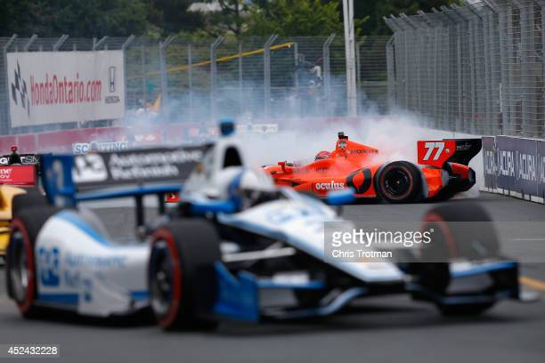 Simon Pagenaud of France driver of the Schmidt Peterson Hamilton Motorsports Dallara Honda is involved in a crash on lap 1 as Helio Castroneves of...