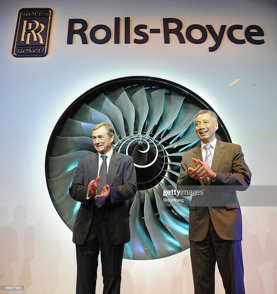 Simon Robertson, chairman of Rolls-Royce Holdings Plc, left, and <a gi-track='captionPersonalityLinkClicked' href=/galleries/search?phrase=Lee+Hsien+Loong&family=editorial&specificpeople=3911578 ng-click='$event.stopPropagation()'>Lee Hsien Loong</a>, Singapore's prime minister, applaud after rotating the fan blades of a Trent 900 engine during a ceremony to launch the company's new facility in Singapore, on Monday, Feb. 13, 2012. Rolls-Royce plans to build 250 Trent engines a year in Singapore and raise the workforce in the city to 2,000. Photographer: Munshi Ahmed/Bloomberg via Getty Images