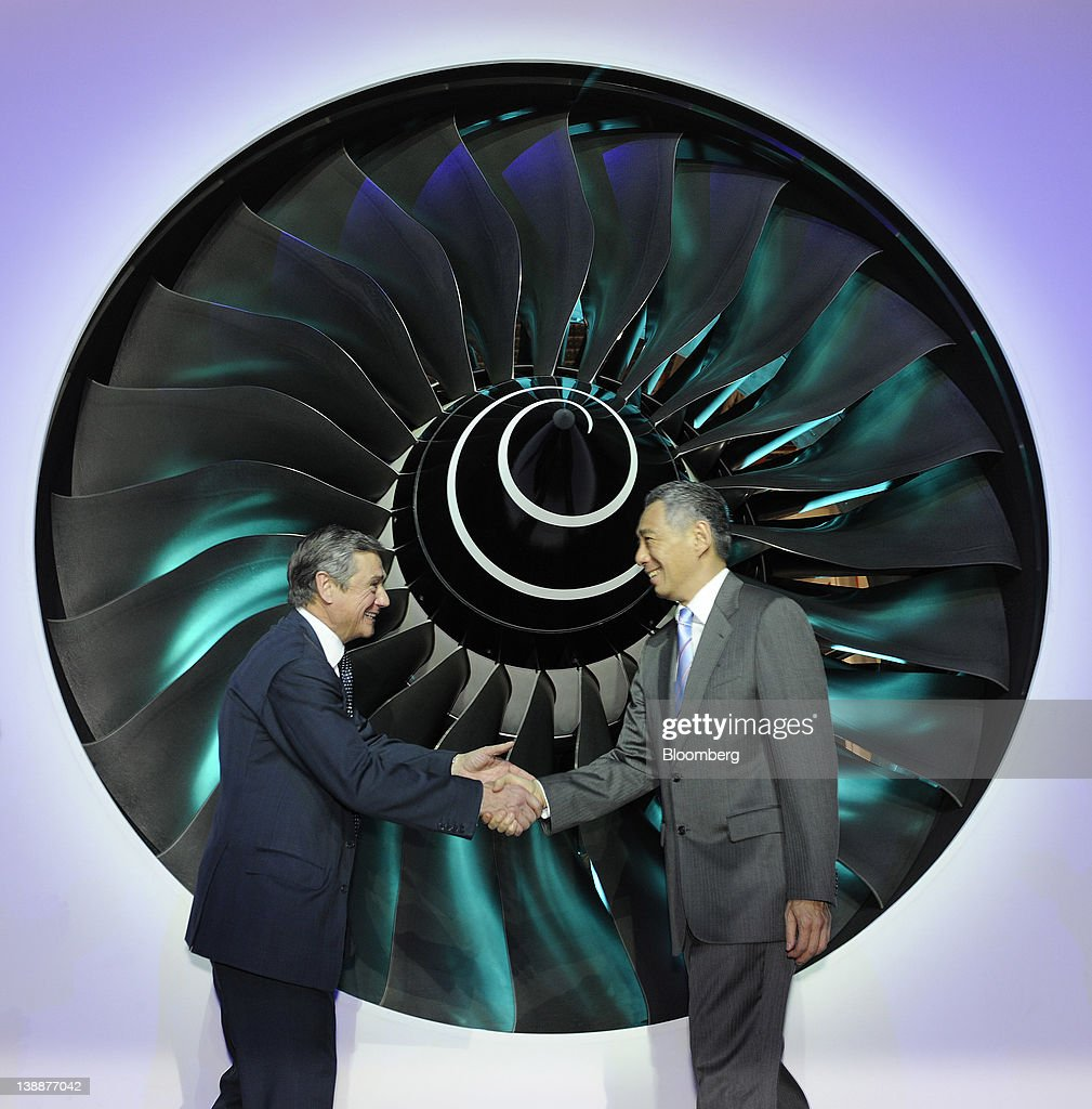 Simon Robertson, chairman of Rolls-Royce Holdings Plc, left, shakes hands with <a gi-track='captionPersonalityLinkClicked' href=/galleries/search?phrase=Lee+Hsien+Loong&family=editorial&specificpeople=3911578 ng-click='$event.stopPropagation()'>Lee Hsien Loong</a>, Singapore's prime minister, after rotating the fan blades of a Trent 900 engine during a ceremony to launch the company's new facility in Singapore, on Monday, Feb. 13, 2012. Rolls-Royce plans to build 250 Trent engines a year in Singapore and raise the workforce in the city to 2,000. Photographer: Munshi Ahmed/Bloomberg via Getty Images