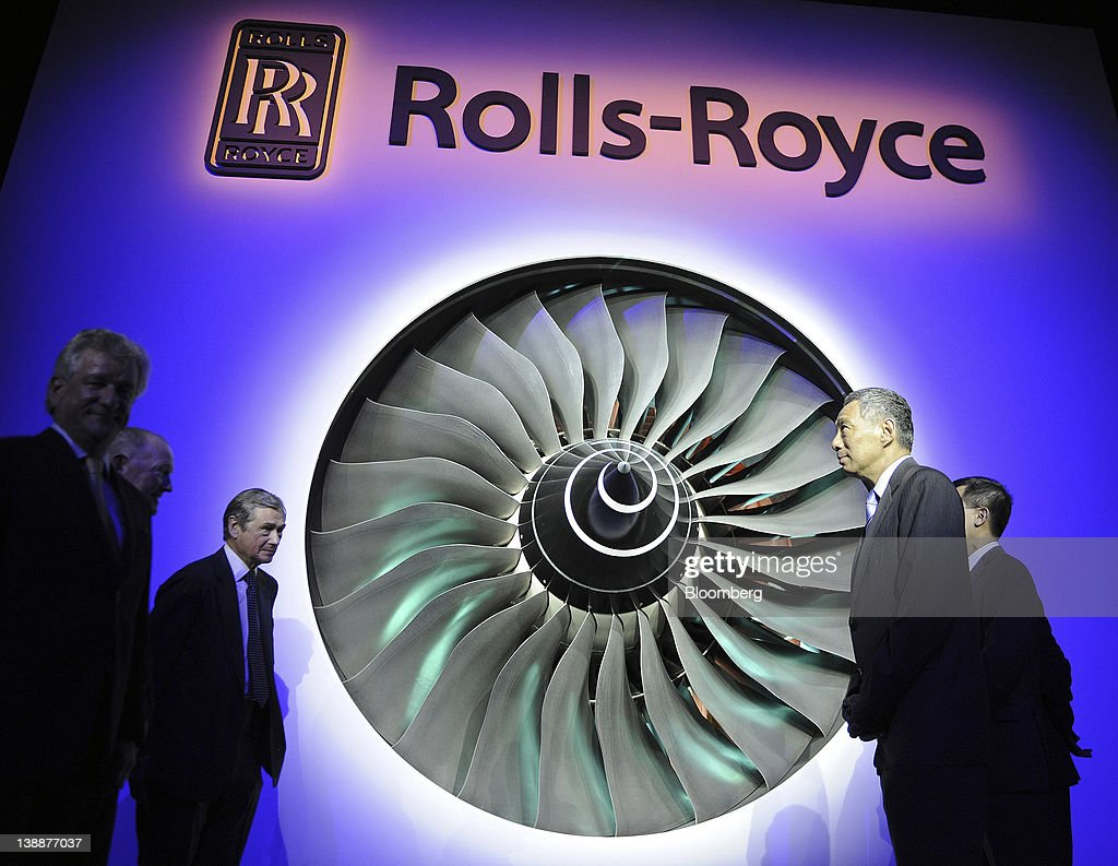 Simon Robertson, chairman of Rolls-Royce Holdings Plc, third from left, and <a gi-track='captionPersonalityLinkClicked' href=/galleries/search?phrase=Lee+Hsien+Loong&family=editorial&specificpeople=3911578 ng-click='$event.stopPropagation()'>Lee Hsien Loong</a>, Singapore's prime minister, second from right, stand before the fan blades of a Trent 900 engine during a ceremony to launch the company's new facility in Singapore, on Monday, Feb. 13, 2012. Rolls-Royce plans to build 250 Trent engines a year in Singapore and raise the workforce in the city to 2,000. Photographer: Munshi Ahmed/Bloomberg via Getty Images