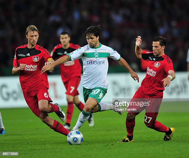 Simon Rolfes and Gonzalo Castro of Leverkusen challenges Diego of Bremen during the DFB Cup Final match between Bayer Leverkusen and Werder Bremen at...