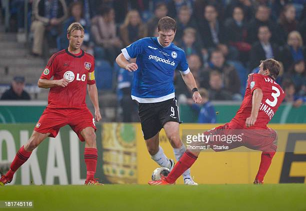 Simon Rolfes and Stefan Reinartz of Leverkusen tackle Fabian Klos of Bielefeld during the DFB Cup match between Arminia Bielefeld and Bayer 04...