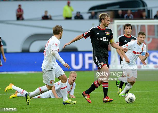 Simon Rolfes of Leverkusen battles for the ball with players of Augsburg during the Bundesliga match between Bayer 04 Leverkusen and FC Augsburg at...