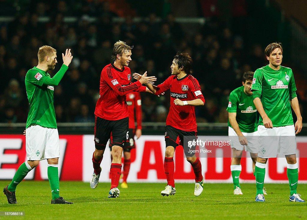 Simon Rolfes of Leverkusen celebrates with his team mate Hajime Hosogai after scoring his team's third goal during the Bundesliga match between...