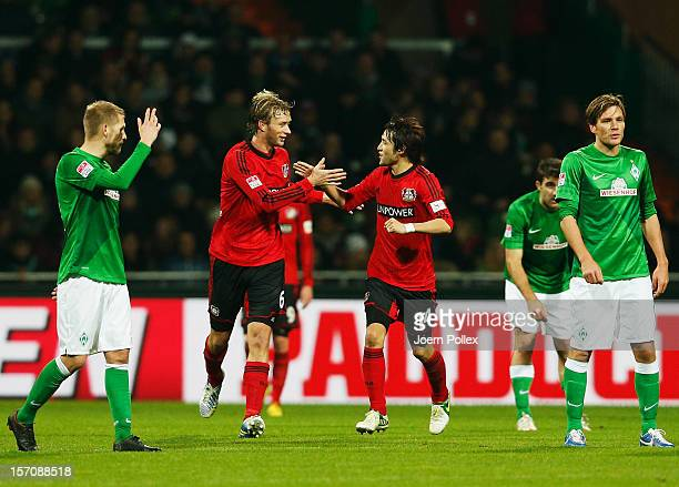 Simon Rolfes of Leverkusen celebrates with his team mate Hajime Hosogai after scoring his team's third goal during the Bundesliga match between...