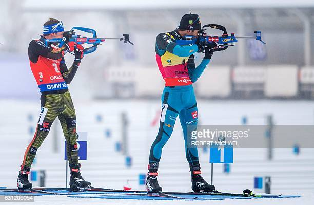 Simon Schempp of Germany and Martin Fourcade of France compete at the shooting range during the men´s 15 km mass start race of the IBU Biathlon World...