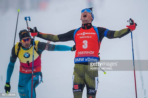 Simon Schempp of Germany celebrates after crossing the finish line in front of third placed Martin Fourcade of France during the men's 15 km mass...